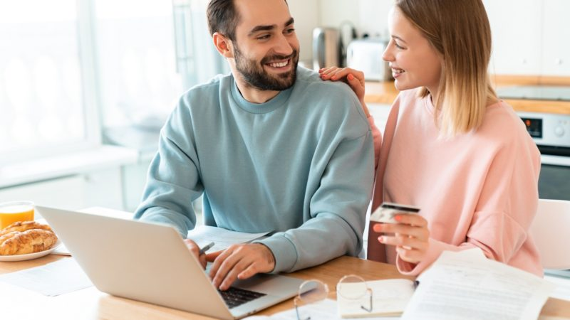 Portrait of young happy couple using credit card while working with laptop and documents in cozy kitchen at home